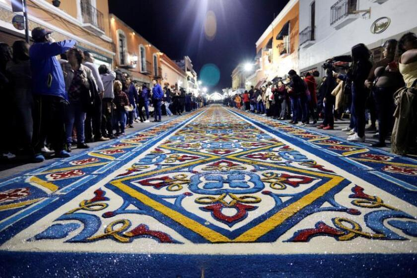 """Cientos de personas observan los coloridos tapetes hechos con aserrín hoy, jueves 15 de agosto de 2019, elaborados por los habitantes de la ciudad de Huamantla, en el estado de Tlaxcala (México), a lo largo de siete kilómetros durante los festejos de la fiesta patronal en conmemoración a la virgen de la Caridad, conocida también como """"La Noche que Nadie Duerme"""". EFE/ Hilda Rios"""