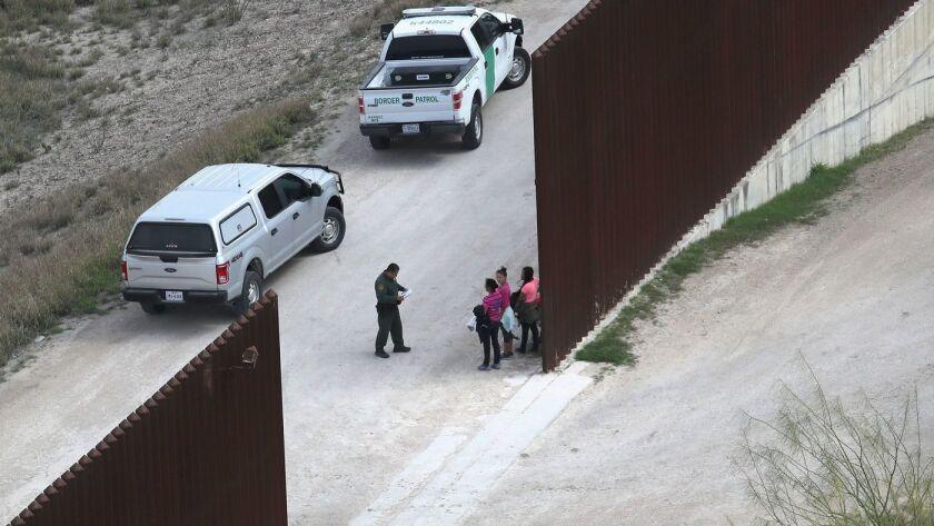 Agentes de la Patrulla Fronteriza de los EE.UU. interrogan a familias de inmigrantes indocumentados en la cerca fronteriza con México, el 21 de febrero pasado, cerca de McAllen, Texas (John Moore / Getty Images).