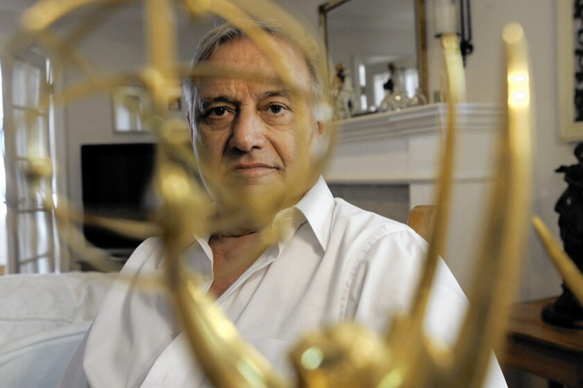 Tony Verna , a former television director, is photographed through one of his Emmys.