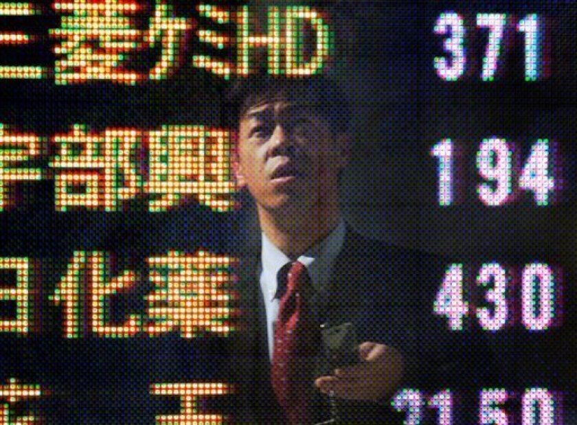 A man checking stock prices is reflected on an electronic stock board of a securities firm in Tokyo, Japan, Friday, Feb. 6, 2009 as Japanese shares climb Friday, Feb. 6, 2009. Japan's benchmark Nikkei 225 stock average gained 126.97 points and closed at 8,076.62 Friday. (AP Photo/Itsuo Inouye)
