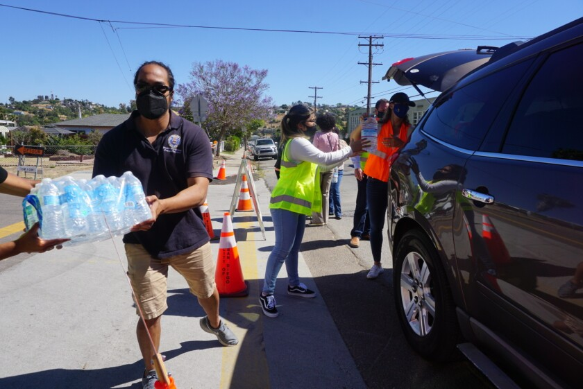 Max Ellorin collects water bottle cases on Friday, June 11, 2021, at the Encanto Recreation Center.