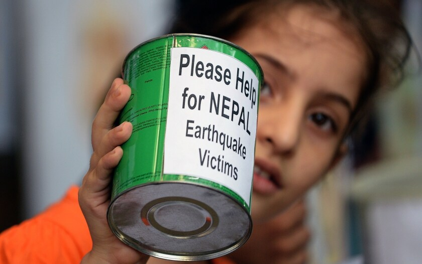 A school child in Mumbai, India, collects funds for victims of the devastating earthquake in Nepal.