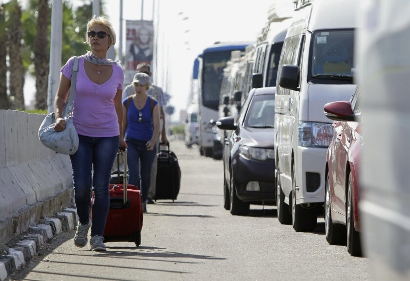 Tourists with their luggage walk towards the main entrance to the Sharm el-Sheikh airport in Egypt on Saturday, Nov. 7, 2015. Egypt's Foreign Minister Sameh Shoukry complained on Saturday that Western governments had not sufficiently helped Egypt in its war on terrorism and had not shared relevant