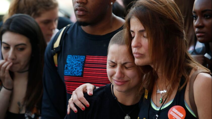 Anti-gun violence advocate and Marjory Stoneman Douglas High School shooting survivor Emma Gonzales, center, is comforted at the End of School Year Peace March and Rally in Chicago on Friday.