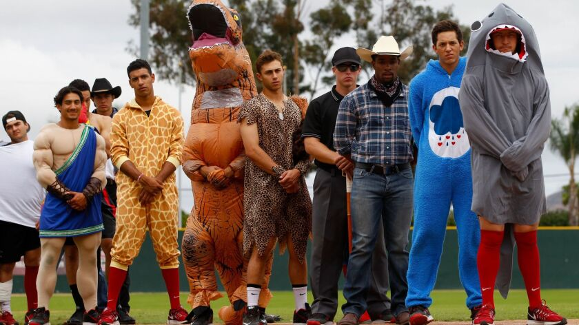 Aztecs baseball players line up for the singing of the National Anthem on Sunday at the annual Halloween scrimmage.