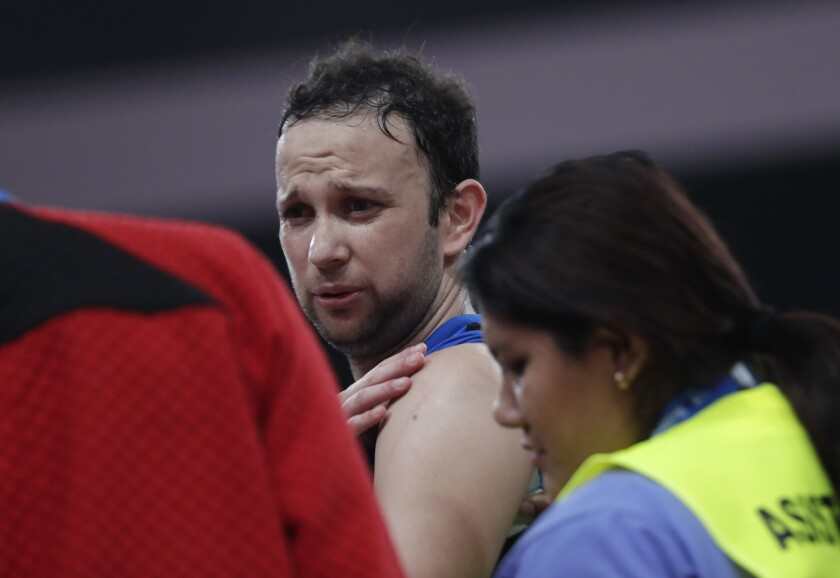 Guatemala's Kevin Cordon touches his shoulder during the badminton men's singles semi-final against Canada's Brian Yang at the Pan American Games in Lima, Peru, Thursday, Aug. 1, 2019. Cordon retired from the match after claiming an injured shoulder. (AP Photo/Silvia Izquierdo)