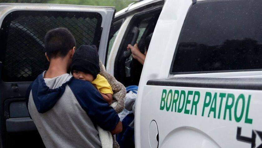 Migrants who crossed the U.S.-Mexico border near McAllen, Texas, are placed in a Border Patrol vehicle.