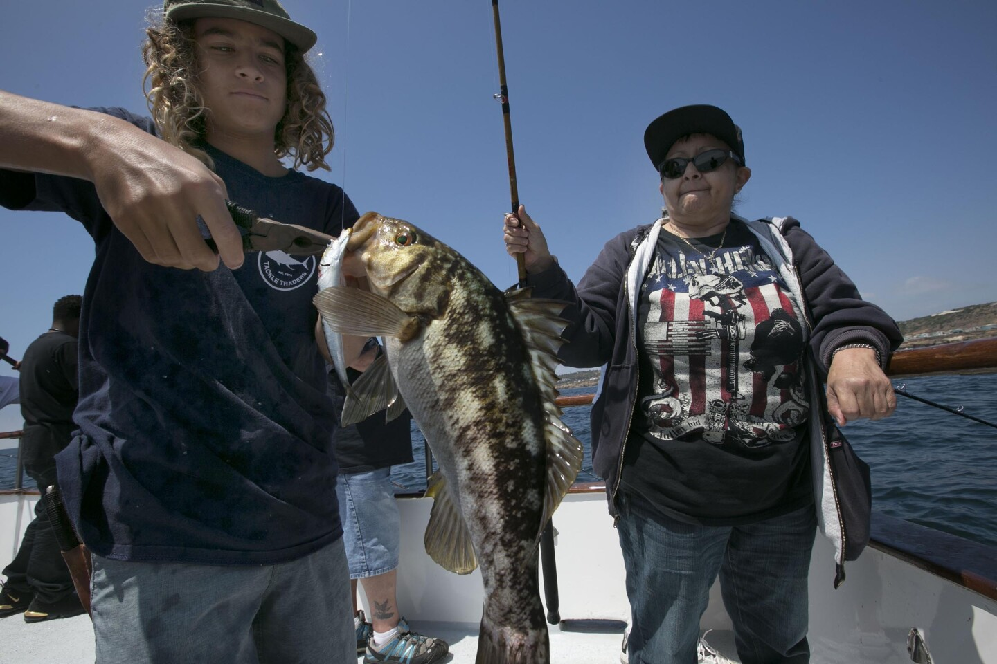 Outpaitient veterans from the Loma Linda VA hospital, like Army veteran Gloria Mauricio, right, getting a hand with an undersize barracuda by deckhand Niko Launais, made a trip to Point Loma on Tuesday, June 18, 2019 to enjoy a fishing trip courtesy of their local Elks Club. The group left the dock at H&M Landing aboard the Fisherman III at 10am and returned at 6pm after a day of bottom fishing off of Point Loma.