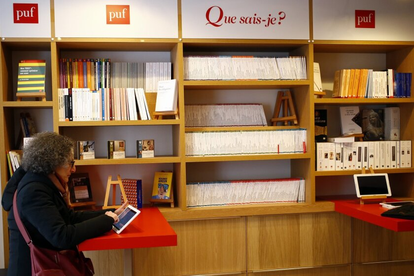 In this Monday, March 14, 2016 photo, French client Zeina Ganadry checks the listing to choose the biography of Montaigne from Stefan Zweig to be print on the Expresso Book Machine at the PUF bookstore in Paris. To many Parisians, the letters PUF have always been associated with the intellectual heart of the French capital. So when the 95-year-old venerable publishing house specializing in human and social sciences was forced to close its historic bookstore on the Place de La Sorbonne in 1999, it left a big void in the heart of many students and researchers. But Les Presses Universitaires de France (PUF) is back in town, just a stone's throw from their previous location in the Quartier Latin neighborhood. (AP Photo/Francois Mori)