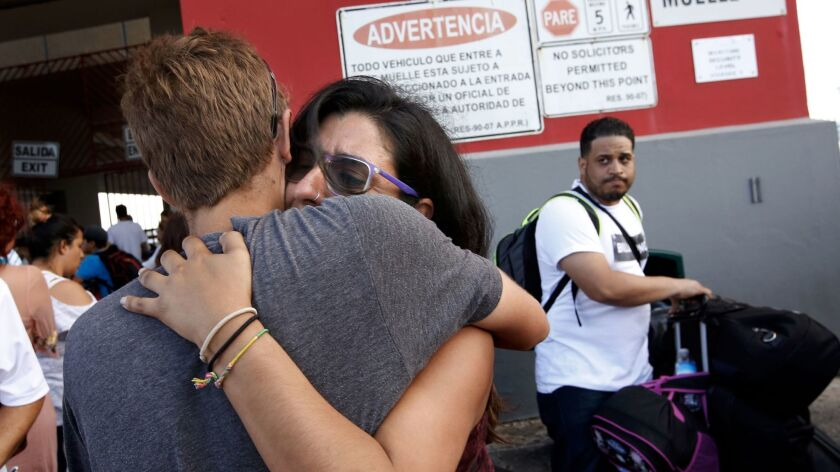 Alejandra Suarez, 30, cries as she embraces her husband, Javier Munoz, on the pier Thursday in San J
