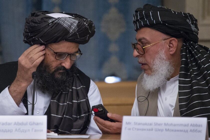 """FILE - In this May 28, 2019, file photo, Mullah Abdul Ghani Baradar, the Taliban group's top political leader, left, and Sher Mohammad Abbas Stanikzai, the Taliban's chief negotiator, talk to each other during a meeting in Moscow, Russia. Taliban officials say several of the group's members have been freed from Afghan jails, including former shadow governors, the first move of its kind since a peace deal that seemed imminent was declared """"dead"""" and just days after a U.S. envoy met with Mullah Abdul Ghani Baradar and other top Taliban leaders in the Pakistani capital of Islamabad. (AP Photo/Alexander Zemlianichenko, File)"""