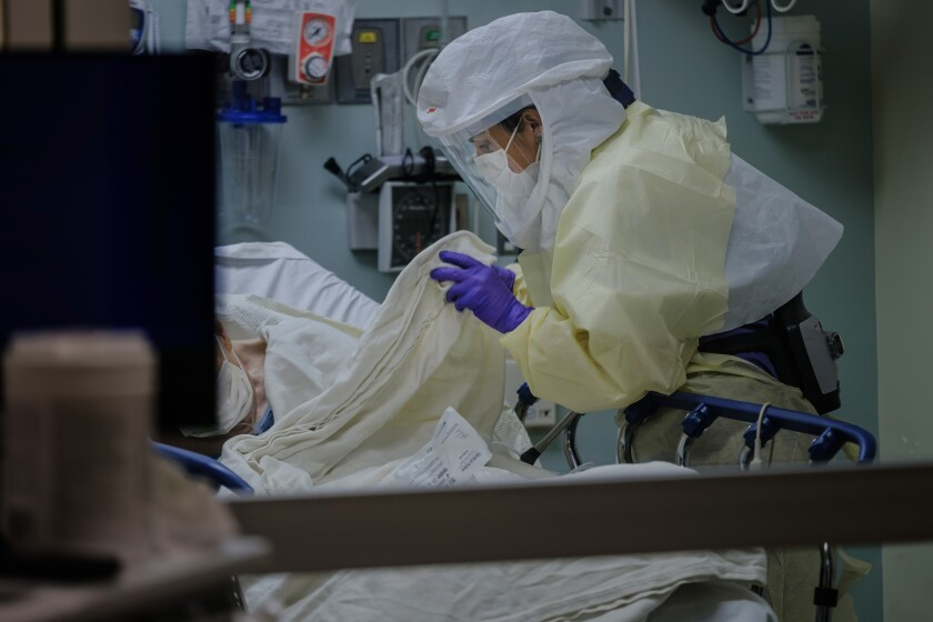 Wearing personal protective equipment, Registered Nurse April Bandi cares for a patient that has possible COVID-19 symptoms inside a special negative pressure isolation room at the Emergency Department at Sharp Memorial Hospital in San Diego on April 10, 2020.