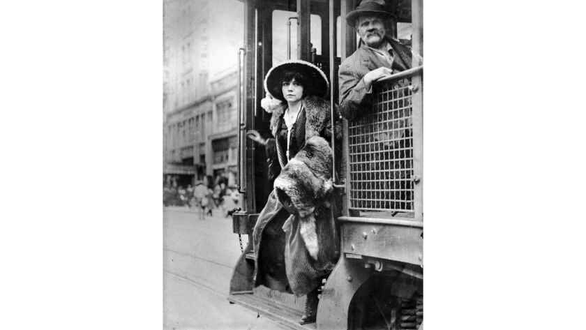 1912 photo of fashionable woman getting off trolley.