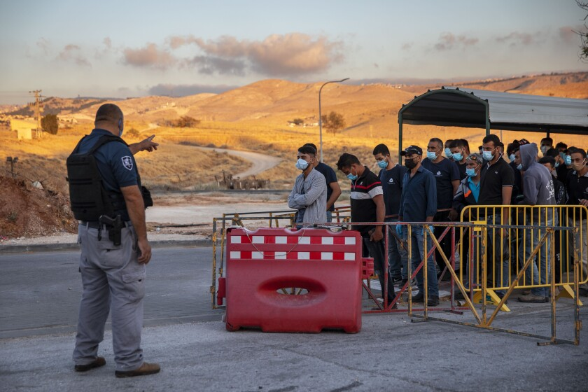 Palestinian laborers line up at a checkpoint to enter the Israeli settlement Maale Adumim.
