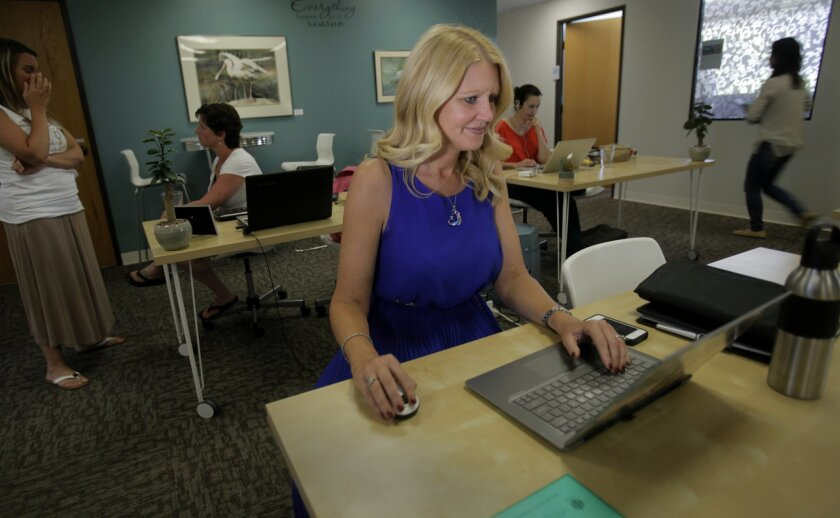 Felena Hanson, founder of Hera Hub, a women's business networking and working space, has recently been named Women in Business Champion of the Year by the San Diego Small Business Association. She works on her laptop in a communal work area while other women do the same.