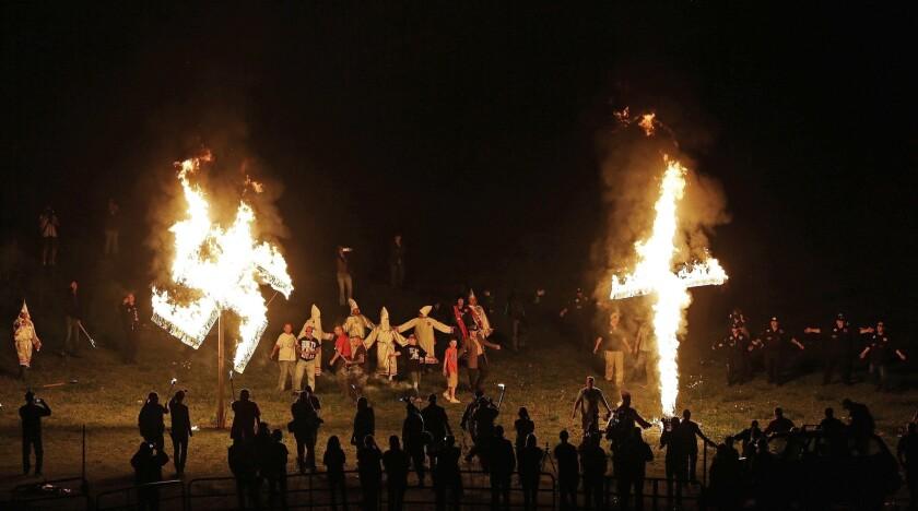"""Miembros del Ku Klux Klan queman una cruz y una esvástica durante un acto para exaltar el """"orgullo blanco"""" cerca de Cedar Town, Georgia. 150 años después de su nacimiento, el KKK sigue vigente, aunque con muchos menos afiliados que en sus mejores momentos, y se enfoca en su oposición a la inmigración, no en los derechos civiles de los negros. (AP Photo/Mike Stewart)"""