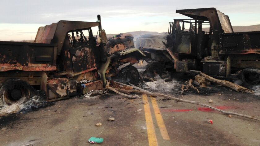 The burned-out husks of heavy trucks sit on Highway 1806 near Cannon Ball, N.D.