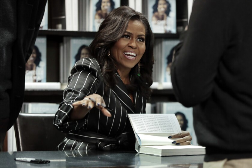 "Former first lady Michelle Obama signs books during an appearance for her book, ""Becoming,"" in New York on Nov. 30, 2018."
