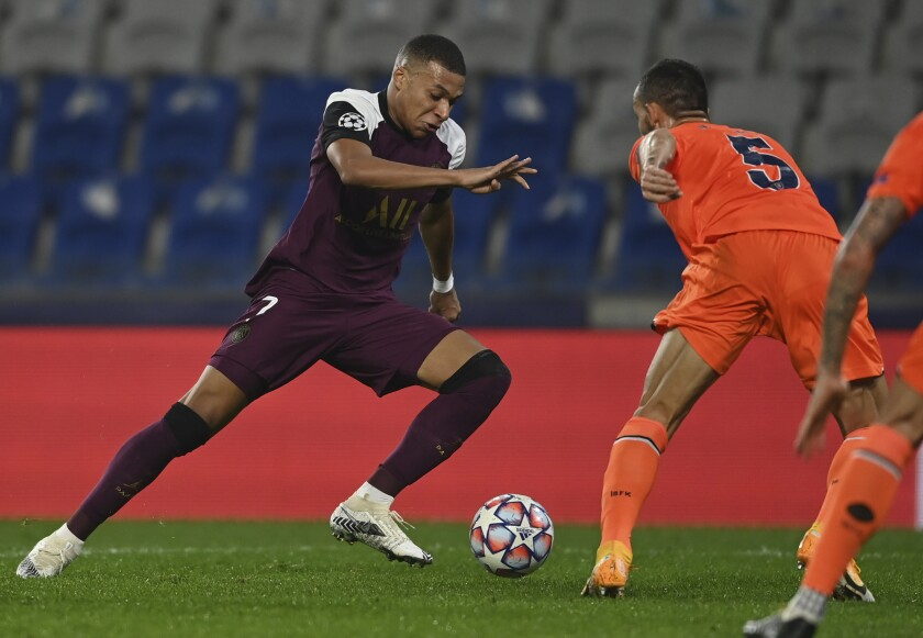 Paris St.-Germain's Kylian Mbappe, left, tries to dribble past Basaksehir's Mehmet Topal.