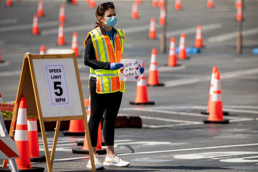 "Cassidy Roosen, with Beach Cities Health District, holds up a sign that says, ""We're All In This Together,"" while waiting to direct cars at a drive-through, appointment-only coronavirus testing location, at the South Bay Galleria, in Redondo Beach."