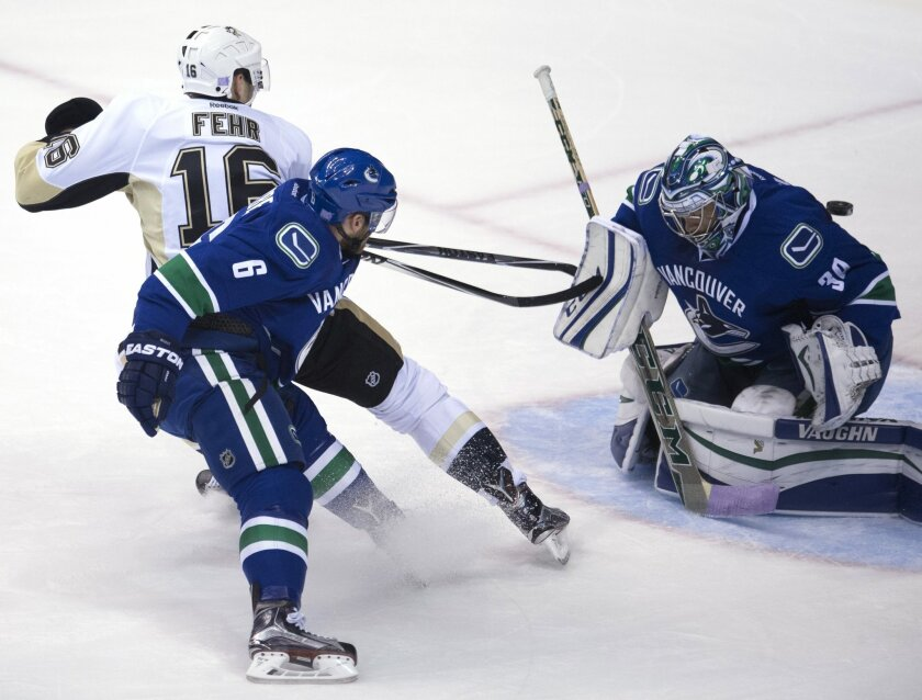 Vancouver Canucks defenseman Yannick Weber, center, watches as Pittsburgh Penguins'right wing Eric Fehr (16) sends his shot past Canucks goalie Ryan Miller during the third period of an NHL hockey game Wednesday, Nov. 4, 2015, in Vancouver, British Columbia. (Jonathan Hayward/The Canadian Press via
