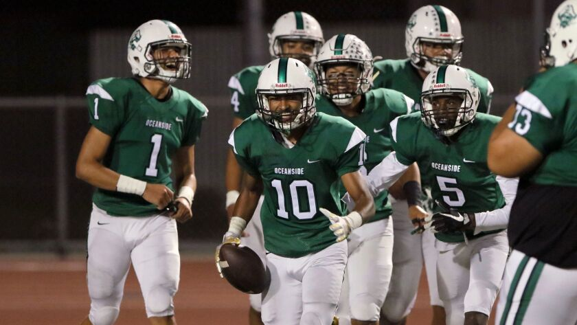 Oceanside's Trejan Apodaca (10) savors his second interception return for a touchdown in the game.