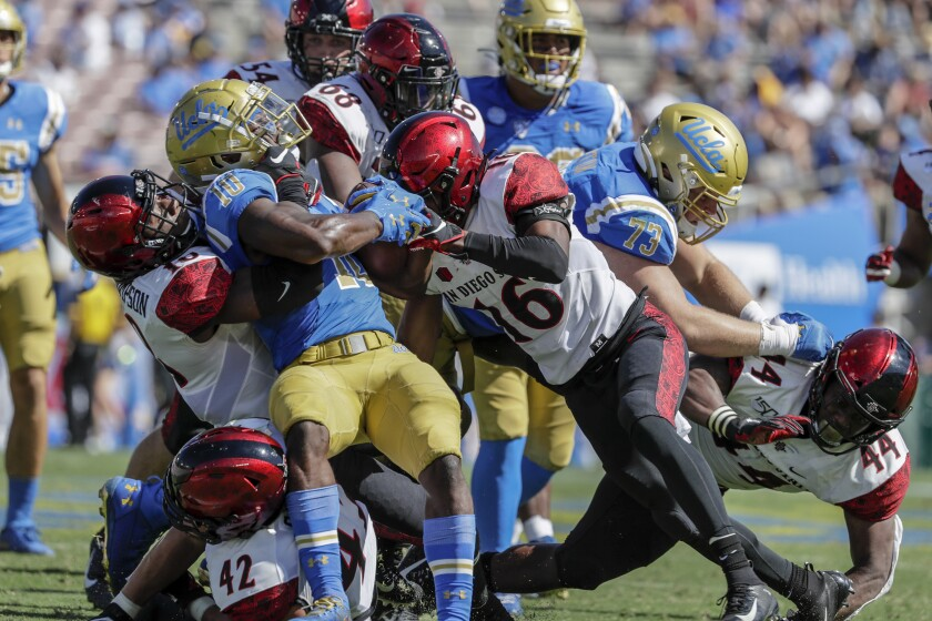 UCLA running back Demetric Felton is gang tackled by San Diego State on Saturday at the Rose Bowl.