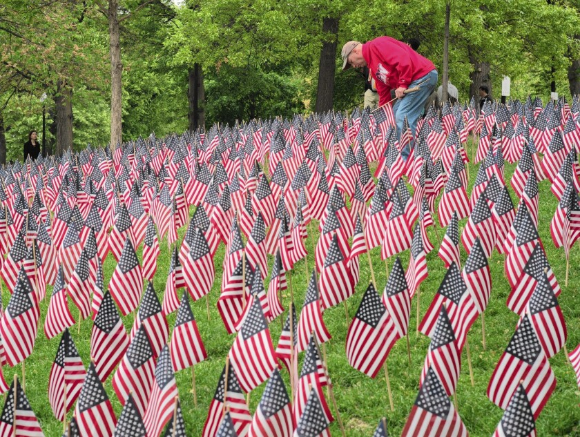 A volunteer tends to the garden of 37,000 flags representing each Massachusetts soldier lost since the Revolutionary War on display on the Boston Common in advance of Memorial Day.