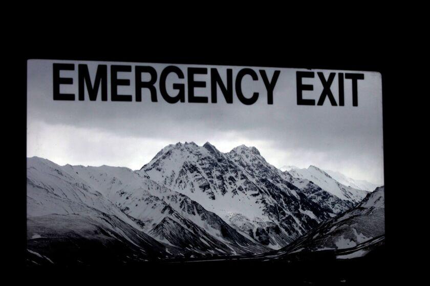 Mountains loom beyond a tour bus window's exit sign in Alaska's Denali National Park.