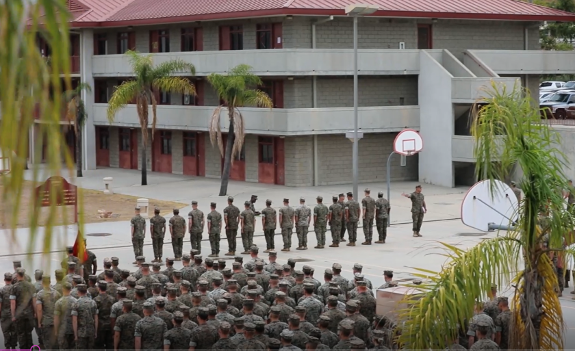 In this video screenshot, the battalion sergeant major for 1st Battalion, 5th Marine Regiment , Sgt. Major Matthew Dorsey, points at a line of 15 Marines as he instructs waiting NCIS agents to arrest them.