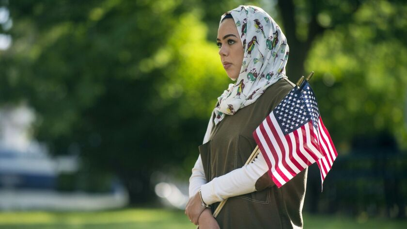 A Muslim woman holds American flags at an interfaith prayer service in Flint, Mich., on June 22.