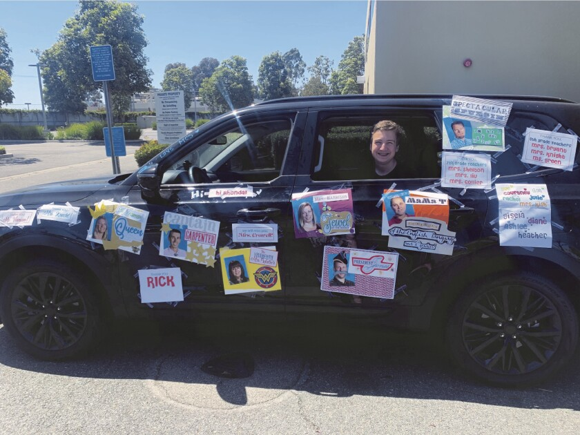 """Clay Riener, an eighth-grader at Costa Mesa's Mariners Christian School, greets teachers at a May 22 """"Drive-Bye"""" on the last day of the school year."""