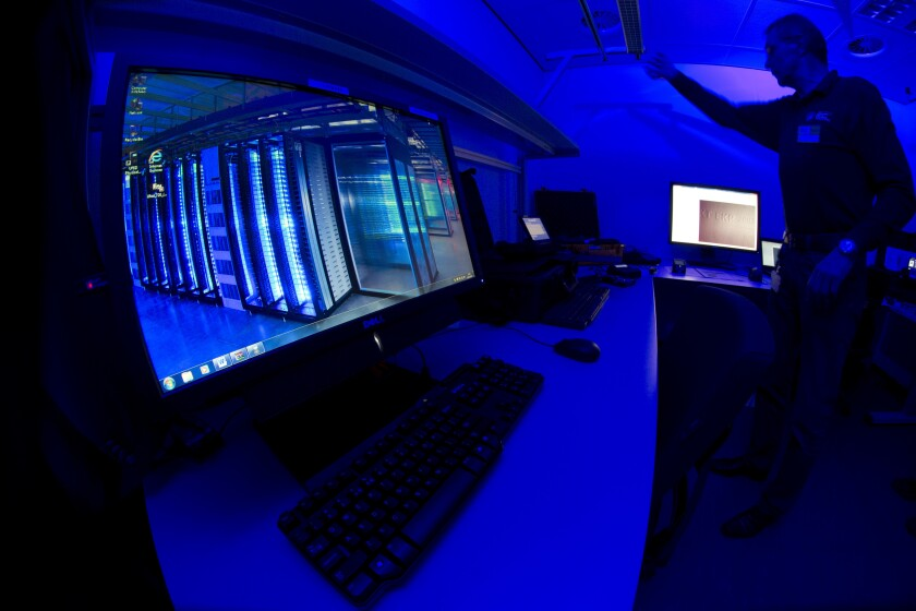 "FILE - This Friday Jan. 11, 2013 file photo of a member of the Cybercrime Center as he turns on the light in a lab during a media tour at the occasion of the official opening of the Cybercrime Center at Europol headquarters in The Hague, Netherlands. Dutch and French police have broken into an encrypted communications network used by organized crime gangs, allowing them to ""look over the shoulders"" of criminals in real time as they planned drug trafficking, arms sales, assassinations and torture, officers announced Thursday. (AP Photo/Peter Dejong, File)"