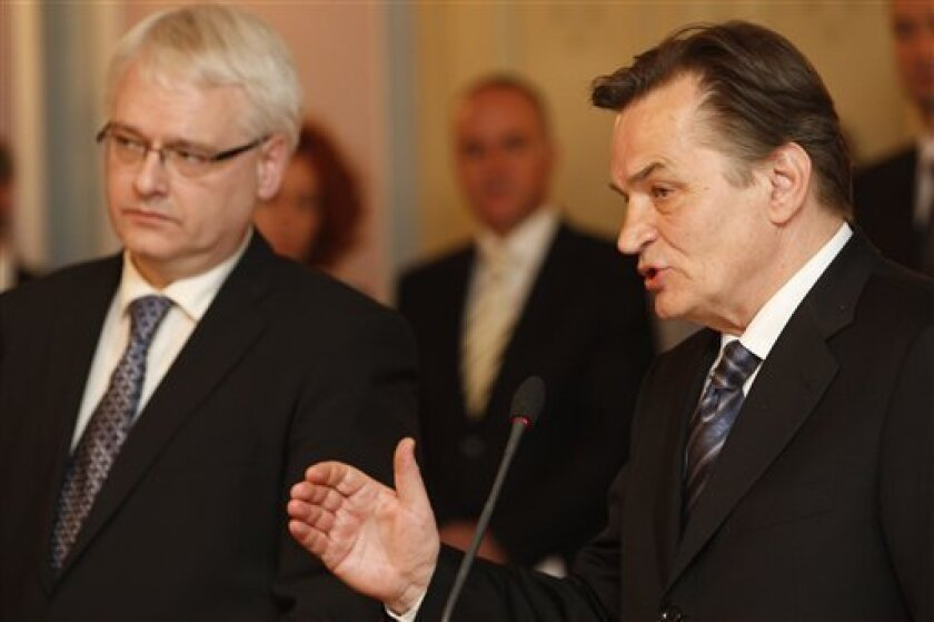 Croatian President Ivo Josipovic, left, accompanied by the chairman of the  Bosnian tri partite presidency, Haris Silajdzic, right, listens as he talks at a press conference during an  official visit to Bosnia, in Sarajevo, Wednesday, April 14, 2010. Josipovic arrived with his delegation for a two-