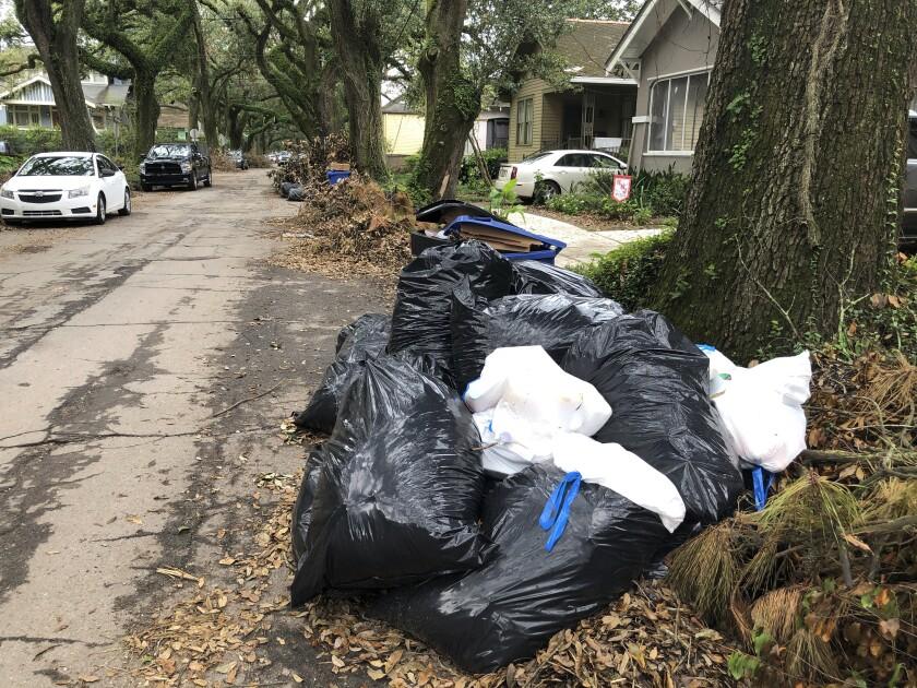 Bolsas y contenedores llenos de basura, así como pilas de escombros, en una calle de Nueva Orleans el viernes 17 de septiembre de 2021. (AP Foto/Kevin McGill)