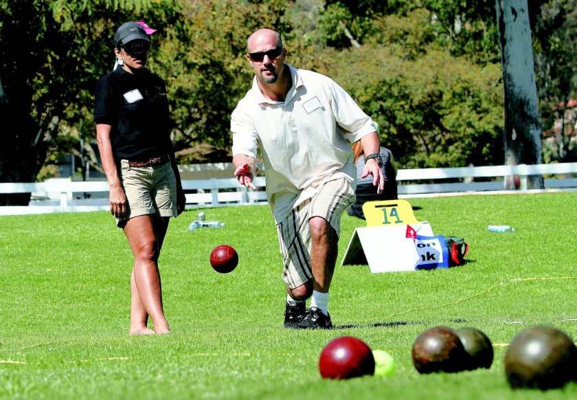 Russell Klapperich of the ETC Building and Design Inc. team makes a toss with teammate Janis Cruz watching during the 16th Annual Turf Bocce Ball Tournament at the Del Mar Horsepark Sunday.