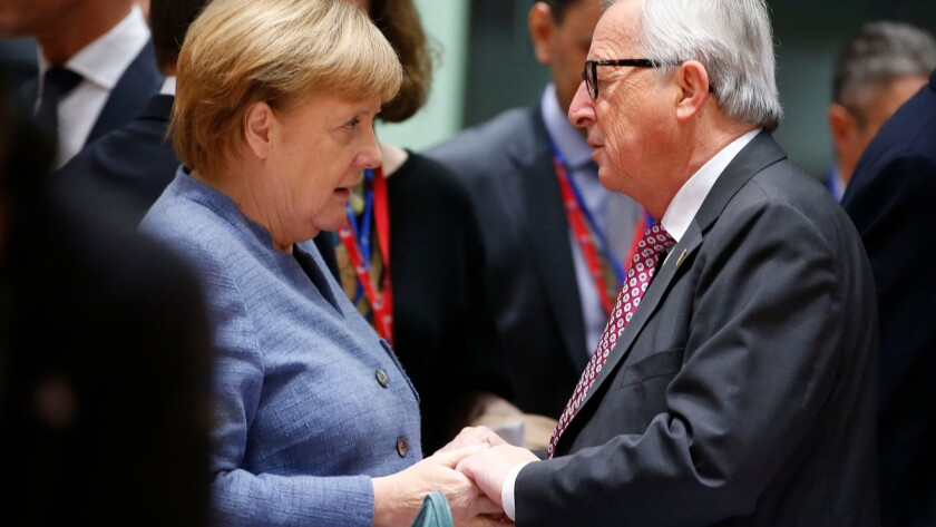 German Chancellor Angela Merkel and European Commission President Jean-Claude Juncker confer at the European Council meeting on the Brexit deal in Brussels.