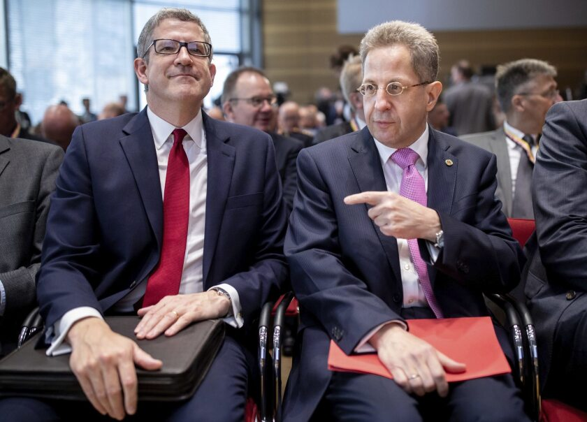 Hans-Georg Maassen, head of the German Federal Office for the Protection of the Constitution, right, talks MI5 head Andrew Parker during symposium on hybrid threat scenarios in Berlin Monday, May 14, 2018.
