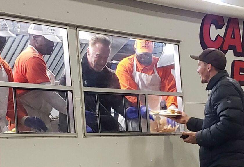 Former California Gov. Arnold Schwarzenegger serves breakfast to firefighters Wednesday, Nov. 21, 2018, in Chico, Calif. Schwarzenegger made a surprise visit to firefighters battling the Camp Fire as light rain started falling in the region.