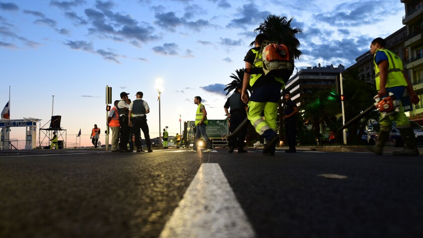 The day after the deadly attack in Nice, workers clean the oceanfront promenade where dozens were killed.