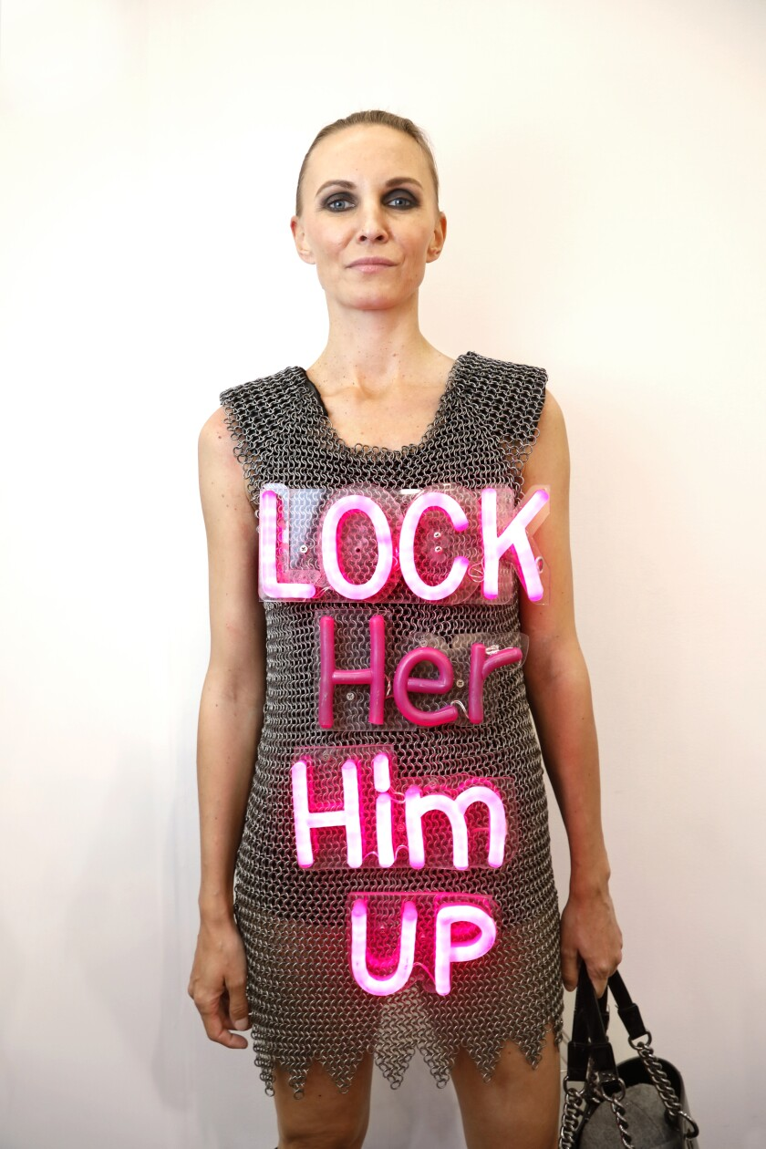 """Gordana Simunovic wears an installation art dress at Frieze Los Angeles: chain-mail style with the words """"Lock Her Him Up"""" in neon pink and """"Lock Him Up"""" lit up."""