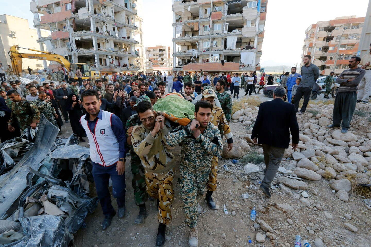 Iranian soldiers carry the body of an earthquake victim near the wreckage of a collapsed building in the city of Pole-Zahab, in Kermanshah province, Iran, on Nov. 13. A 7.2 magnitude earthquake that struck Iran's the province bordering Iraq has killed more than 328 people and left at least 3,950 injured, Iranian authorities said.