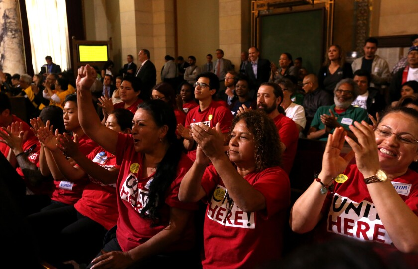 Supporters applaud after the Los Angeles City Council tentatively agreed Tuesday to raise the city's minimum wage to $15 per hour.