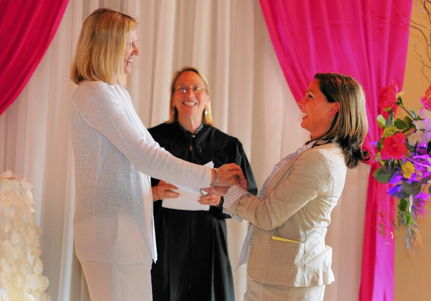 """Julie Engbloom, left, and Laurie Brown are married by Judge Beth A. Allen in Portland. """"The biggest question was, 'Oh, my God, what to wear?'"""" Engbloom said."""