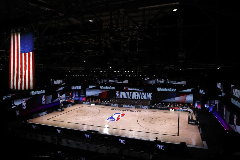 An empty court and bench are shown following the scheduled start time between the Milwaukee Bucks and Orlando Magic.