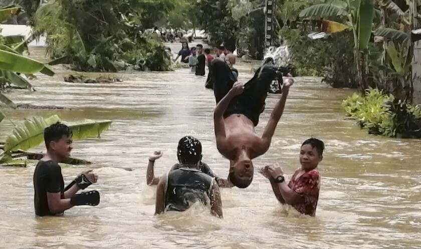 Residents play along floodwaters caused by typhoon Conson at Ormoc City, Leyte province, Philippines on Tuesday Sept. 7, 2021. Typhoon Conson slammed into the eastern Philippines, causing power outages, suspension of work in government offices, and flooding in some areas on Tuesday. Weather bureau later said Conson weakened into a severe tropical storm. (AP Photo/Roberto Dejon)