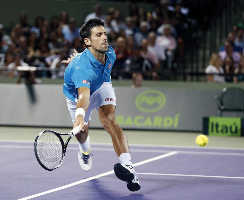 Novak Djokovic, of Serbia, chases the ball hit by Tomas Berdych, of the Czech Republic, at the Miami Open tennis tournament, in Key Biscayne, Fla., Wednesday, March 30, 2016. (AP Photo/Joel Auerbach)