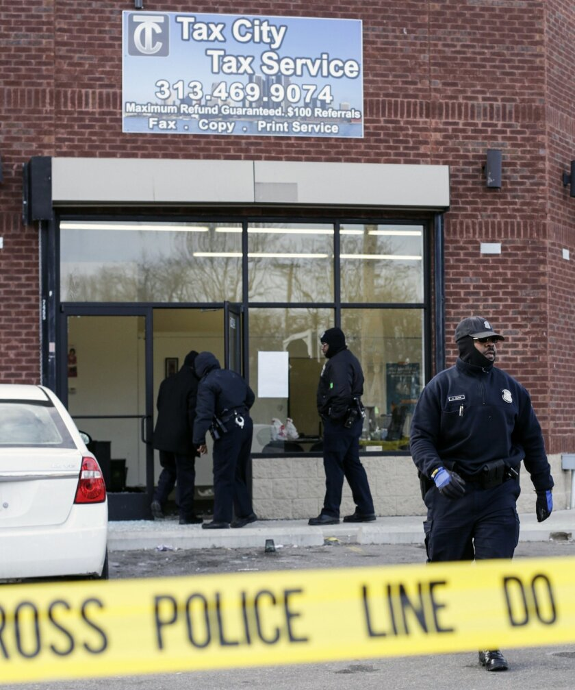 Detroit Police Officers check out the scene after a shooting injuring four people at a tax preparation business in Detroit, Friday, Feb. 28, 2014. Deputy Police Chief Rodney Johnson said a woman became upset when her tax refund wasn't ready Friday and started scuffling with the guard. Johnson said