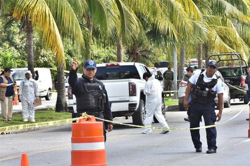 Peritos forenses inspeccionan la zona en la que hubo un enfrentamiento entre bandas rivales este sábado, en Cancún (México) y que dejó tres muertos y un herido según informaron las autoridades locales. EFE