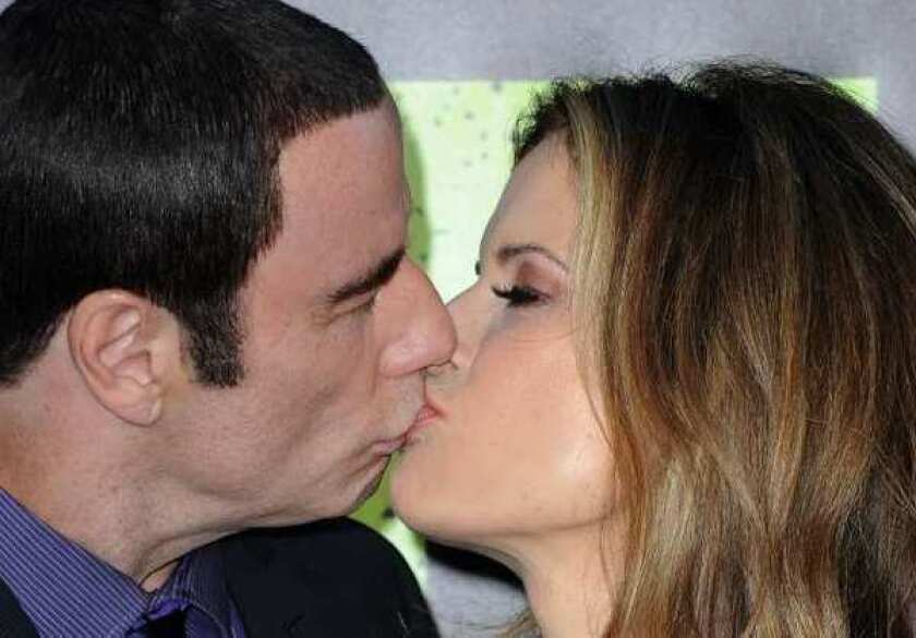 """John Travolta and his wife, Kelly Preston, kiss as they arrive for the premiere of Universal Pictures' """"Savages"""" at Westwood Village."""